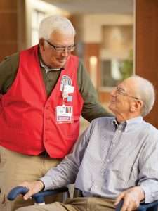 Volunteer greets patient during visit.
