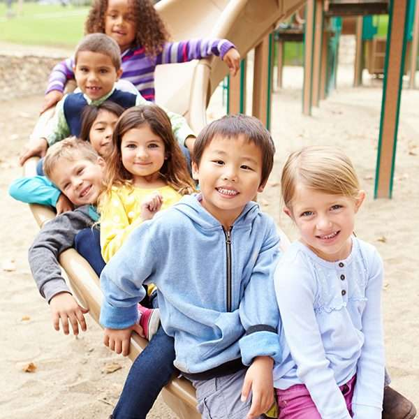 Group Of Young Children Sitting On Slide In Playground Smiling To Camera